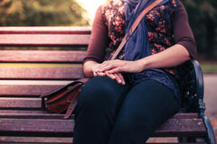 Young woman sitting on park bench Stock Photo