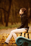Young woman sitting on park bench in the autumn Royalty Free Stock Photos