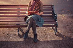 Young woman sitting on park bench with book Stock Photography