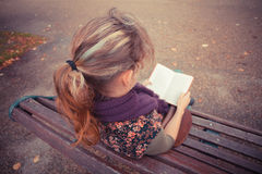 Young woman sitting on park bench with book Stock Image