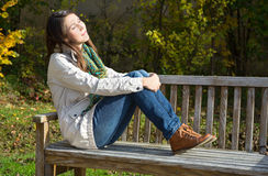 Young woman sitting on a park bench and enjoy the autumn. Stock Photography