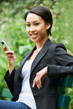 Young Woman Sitting On Park Bench Reading Text Message Royalty Free Stock Photos