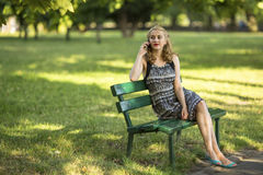 Young  woman sitting on a Park bench talking on a cell phone. Royalty Free Stock Photography