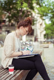 Young woman sitting on a park bench working Stock Photo