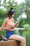 Texting to friends. Young woman sitting in park, drinking cocktails and texting to friends Stock Photography