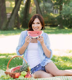 Young woman sitting in the park and eating a watermelon. stock photos