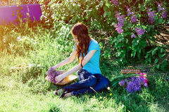 Young woman sitting in the park on the grass with flowers Stock Photography