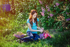 Young woman sitting in the park on the grass with flowers Royalty Free Stock Images
