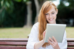 Young woman sitting in a park with her tablet-pc Stock Photos