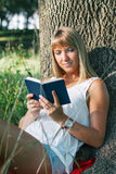 Young woman sitting in the park and reading a book Royalty Free Stock Image