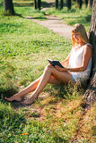Young woman sitting in the park and reading a book Stock Image