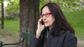 Young woman sitting in the Park talking on the phone. stock footage