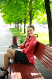 Young woman sitting in a park talking on the phone Royalty Free Stock Image