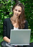 Young woman sitting in park and using laptop Stock Image