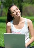 Young woman sitting in park and using laptop. Lovely young woman sitting on grass  in park and using laptop Royalty Free Stock Photography