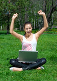 Young woman sitting in park and using laptop. Excitement young woman with raised arms sitting on grass  in park and using laptop Royalty Free Stock Images