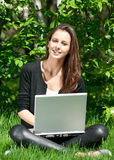 Young woman sitting in park and using laptop. Lovely young woman sitting on grass in park and using laptop Stock Image