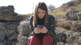 Young woman sitting in the park, using smartphone. Pretty Girl using smartphone at the open air stock video footage
