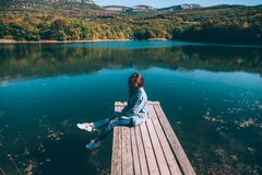 Person sitting on peer by the lake royalty free stock photo