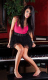 Young woman sitting on piano Royalty Free Stock Photos