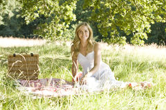 A young woman sitting on a picnic blanket Royalty Free Stock Photos
