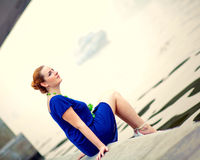 Young woman sitting on a pier Stock Photos