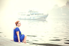 Young woman sitting on a pier Royalty Free Stock Images