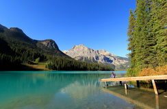 Young woman sitting on a pier at Emerald Lake, Yoho National Par Stock Photography