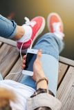 Young woman sitting on pier holding a smartphone Stock Photography
