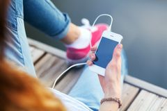 Young woman sitting on pier holding a smartphone Royalty Free Stock Photo