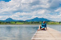 Young woman sitting on pier at lake hopfen Stock Images