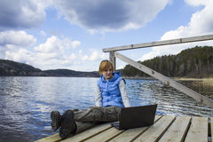Young Woman Sitting on Pier with Laptop Stock Photography