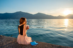 Young woman sitting on the pier at sunrise Stock Image