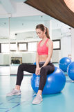 Young woman sitting on pilates ball in the gym Royalty Free Stock Photos