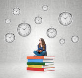 Young woman sitting on pile of books with hanging clocks around Royalty Free Stock Photo
