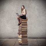 Young woman sitting on a pile of books Royalty Free Stock Photos