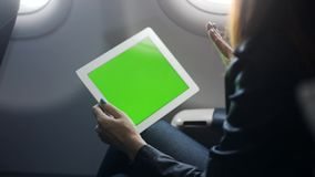 Young woman is sitting at plane and talking with friend or business partner by online conference on tablet stock footage