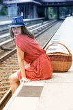Young woman sitting on platform at train station Stock Photo