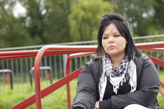 Young Woman Sitting In Playground Royalty Free Stock Images
