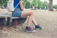 Young woman sitting on playground equipment outside Stock Photos