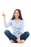 Young woman sitting and pointing Stock Photo