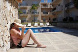 A young woman sitting by the pool Royalty Free Stock Images