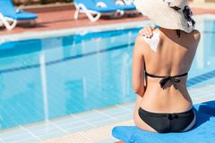 Young woman is sitting by the pool and applying sun cream on her shoulder by the pool. Sun Protection Factor in vacation, concept.  royalty free stock images