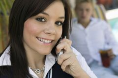 Young woman sitting by pool on cell phone portrait close up Stock Images