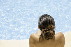 Young woman sitting on the pool edge stock images