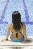 Young woman sitting by the pool Stock Photography