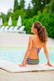 Young woman sitting at poolside Stock Photos