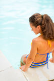 Young woman sitting at poolside. Rear view Stock Image