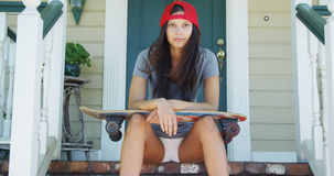Young woman sitting on porch with skateboard Royalty Free Stock Image