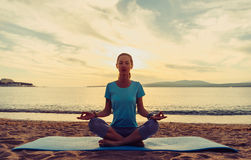 Young woman sitting in pose of lotus. Young woman meditating in pose of lotus on sand beach near the sea at sunset in summer, front view Royalty Free Stock Images